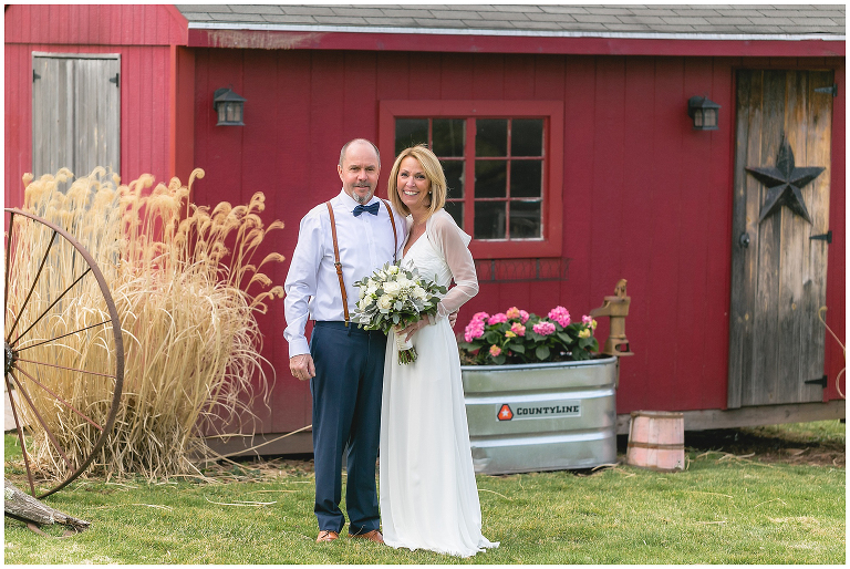 bride and groom in their backyard in front of shed